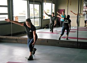 Kristi McGee leads a workout in the studio with windows that open onto the shoreline.