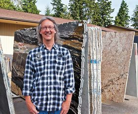 "Bill Wyman stands among granite slabs in the ""bone yard"" at Creative Countertops in Poulsbo."