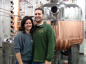 "Heritage Distilling Co. owners Justin and Jennifer Stiefel stand in front of a 2,000-liter pot still, which was custom-made in Italy and they call ""Nona."""
