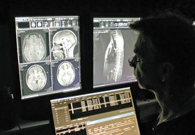 Dr. Manfred Henne looks at images from an MRI scan at his clinic.