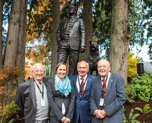 Sculptor Mardie Rees stands with Shawnigan Lake School alumni Stuart Milbrad of Bremerton, left, Francois Elmaleh and John Burr in front of the sculpture Rees created of the school's founder, C.W. Lonsdale. (Photo courtesy Shawnigan Lake School)