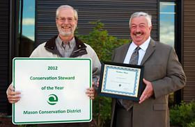 Mason Conservation District manager John Bolender, left, and Tom Farmer, PUD 3 commission president, show off the stewardship sign and award certificate. (Mason County PUD photo)