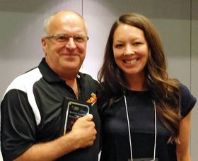 Mark Schaefer, manager of Hop Jack's restaurant in Silverdale, receives an Outstanding Employer Award from Heidi Scheibner, program manager with the Kitsap office of Trillium Employment Services, at the Community Employment Alliance fall conference in Bremerton on Oct. 2. (Photo courtesy Trillium Employment Services)