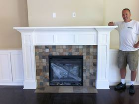 Scott McIntosh stands by a fireplace mantel he built at a home in the Canterwood community in Gig Harbor. (Courtesy photo)