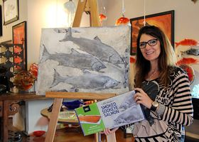 Silverdale artist Lisa Stirrett holds a prototype of this year's Trident Foods smoked salmon box being sold at Costco. Her original painting for the box is on the easel. (Rodika Tollefson Photo)