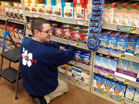 A part-time employee who was placed at Trader Joe's in Silverdale through a supported employment program does his job keeping merchandise properly arranged on store shelves. (Photo courtesy Trillium Employment Services)