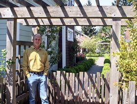 Charlie Wenzlau stands outside of Ericksen Cottages, a pocket neighborhood he designed in downtown Bainbridge. The community includes 11 small-footprint cottages situated around a common courtyard (part of which can be seen behind him.)