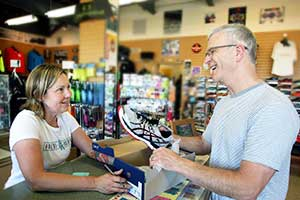 "Photo credit: Larry Steagall) (Caption for photo slugged ""Poulsborun1"": Poulsbo Running owner Brooke Hammett, left, helps regular customer Larry Asher of Poulsbo with a new pair of running shoes. Hammett and her husband, Chris, organize the Roots Rock Trail Running series.)"