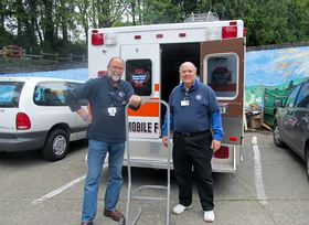 "Retired physicians and West Sound Free Clinic volunteers Dr. Pat Tracy, left, and Dr. Jim Baker stand next to the clinic's ""headquarters,"" a retired ambulance, at a Stand Down for Vets event last April. (Courtesy photo)"