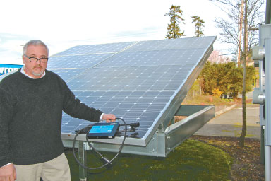 Kelly Samson stands next to an itek Energy solar panel array outside the APS America and Blue Frog Solar LLC headquarters in Poulsbo, holding a third-generation microinverter that connects to four solar modules and is currently being beta-tested. This solar array is the only installation in North America that has the new product. Photo by Rodika Tollefson